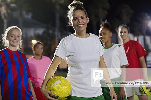 Portrait lächelndes  selbstbewusstes junges weibliches Fußballteam mit Ball auf dem Spielfeld bei Nacht