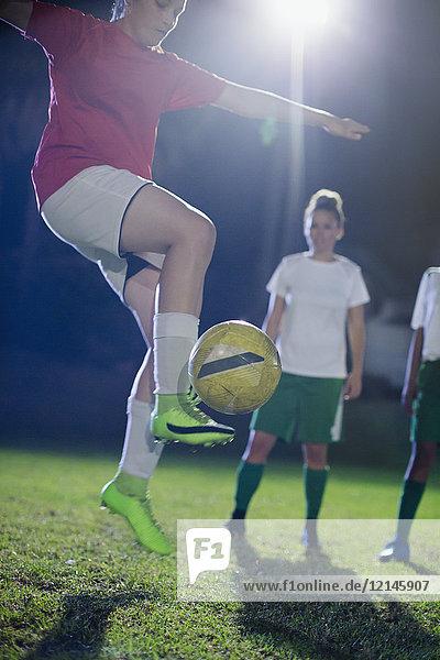 Junge Fußballspielerin übt, springt und tritt den Ball nachts auf dem Spielfeld.