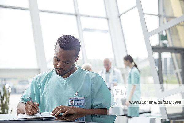 Krankenschwester überprüft Krankenakte in der Lobby des Krankenhauses