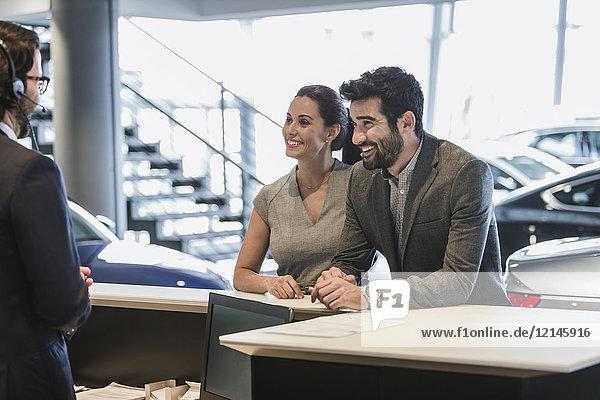 Paar Kunden im Gespräch mit der Rezeption im Autohaus-Showroom