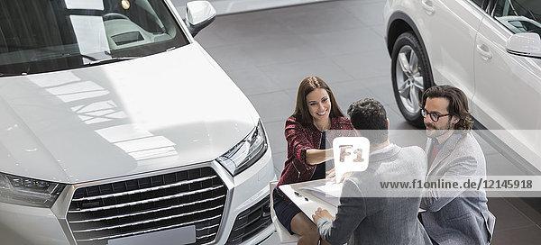 Autoverkäufer beim Händeschütteln mit Kundin im Autohaus-Showroom