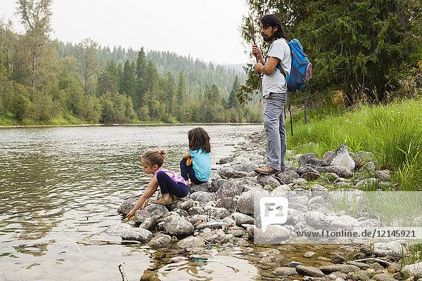 Vater und Töchter beim Wandern, Ausruhen am Seeufer