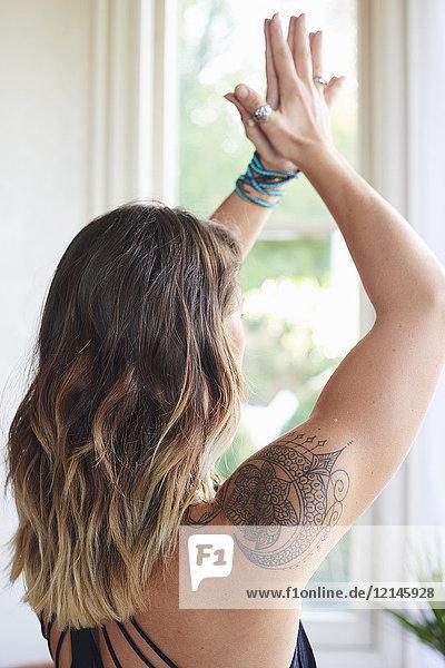 Gelassene Frau mit Tätowierung, die Yoga praktiziert, mit den Händen über Kopf gefasst.