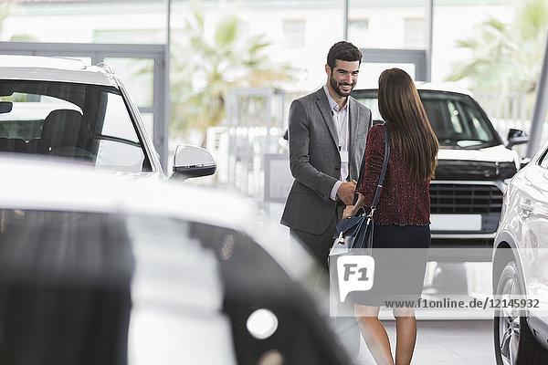 Autoverkäufer-Gruß, Händeschütteln mit Kundin im Autohaus-Showroom