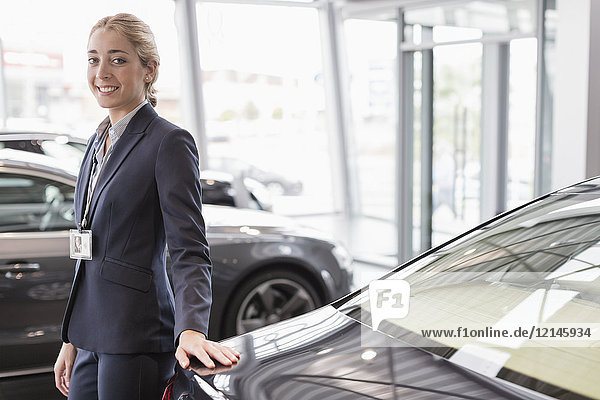 Portrait selbstbewusste Autoverkäuferin im Autohaus-Showroom