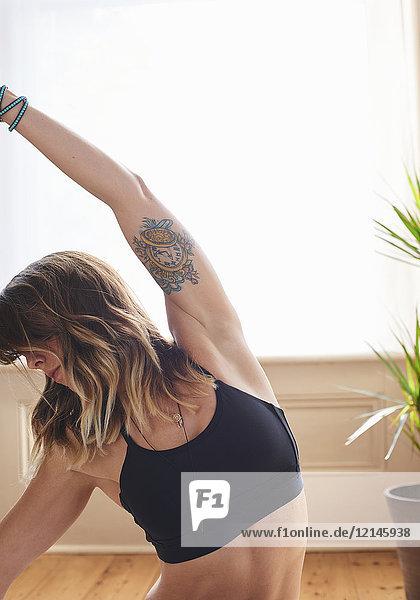 Starke  flexible Frau mit tätowierendem Yoga-Seitenkörper-Stretch