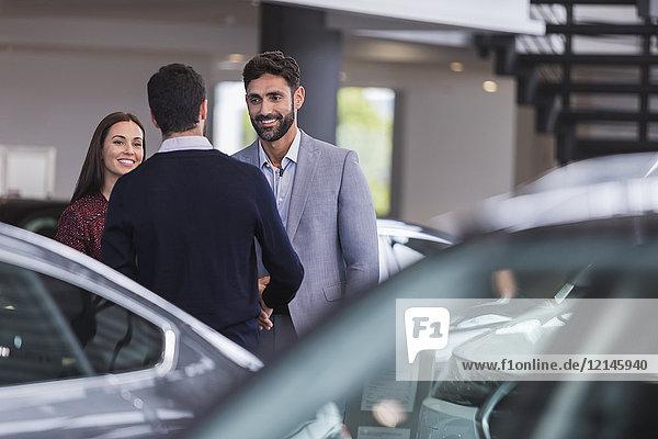 Autoverkäufer-Gruß  Händeschütteln mit ein paar Kunden im Autohaus-Showroom