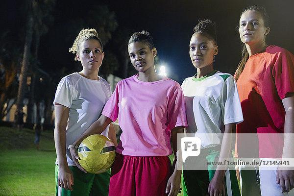 Portrait selbstbewusstes, zähes, junges Frauen-Fußballteam mit Fußball auf dem Spielfeld bei Nacht