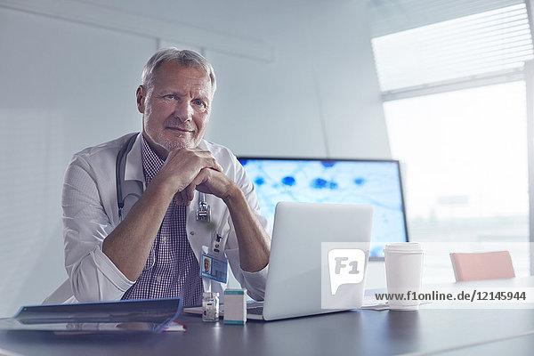 Porträt selbstbewusster Mediziner am Laptop im Krankenhaus