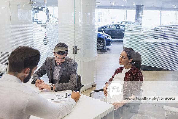 Autoverkäufer erklärt den schwangeren Paarkunden im Autohaus die finanziellen Vertragsunterlagen