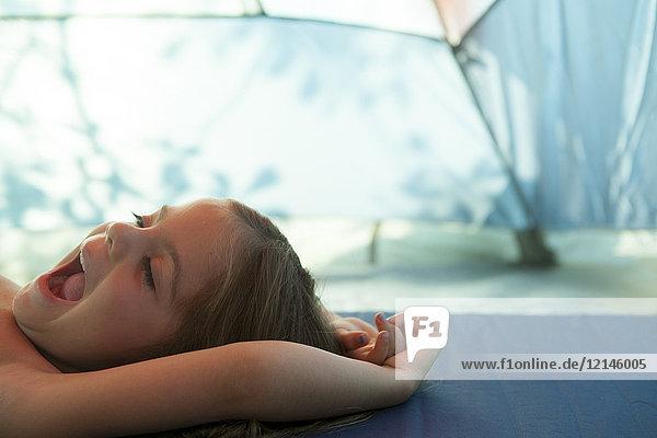 Müdees Mädchen gähnt, ruht sich im Zelt aus.