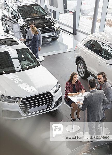 Autoverkäufer treffen sich am Tisch im Autohaus-Showroom
