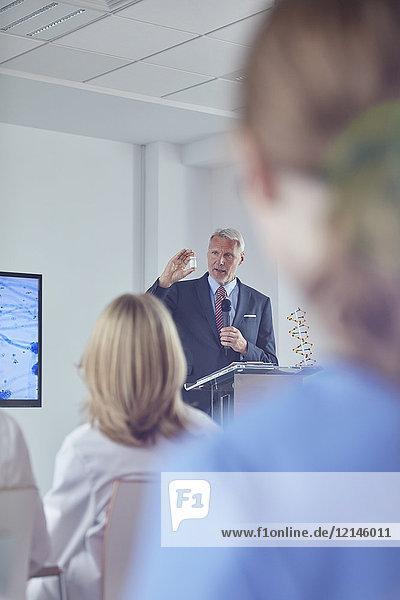 Pharmazeutischer Geschäftsmann erklärt Medikamente auf dem Podium der Konferenz
