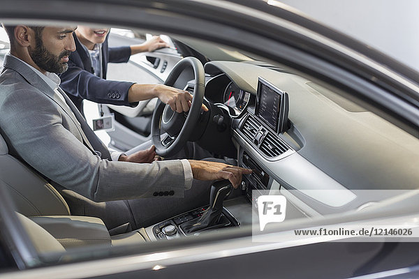 Autoverkäuferin zeigt, erklärt Neuwagen dem männlichen Kunden auf dem Fahrersitz