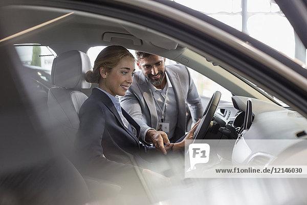Autoverkäufer erklärt Neuwagen der Kundin auf dem Fahrersitz im Autohaus-Showroom