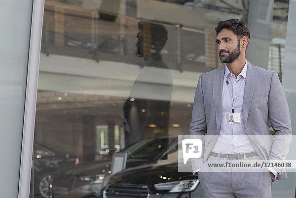 Porträt eines selbstbewussten Autoverkäufers, der außerhalb des Autohauses schaut.