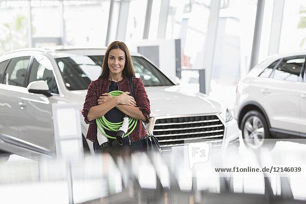 Portrait lächelnde Kundin mit Hybrid-Ladekabel im Autohaus-Showroom