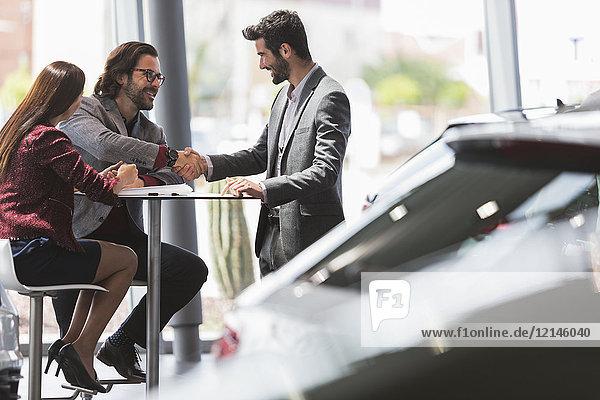 Autoverkäufer beim Händeschütteln mit zwei Kunden am Tisch im Autohaus-Showroom
