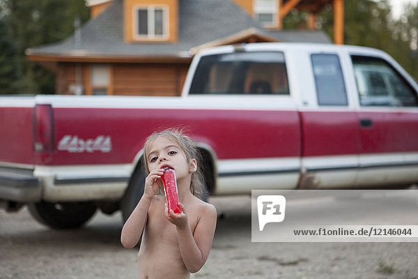 Portrait nacktes Mädchen trinkt Saft in der Nähe von Pickup-Trick