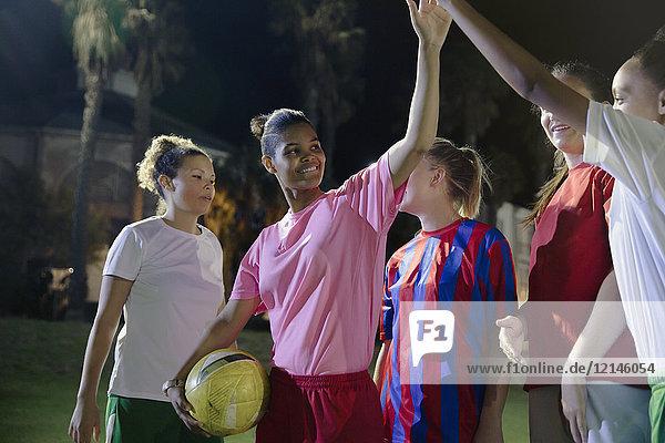 Selbstbewusste junge Fußballmannschaftskameradinnen bei Nacht auf dem Spielfeld