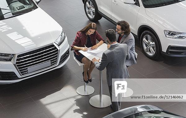 Autoverkäufer beobachtet Paar Kunden bei der Unterzeichnung finanzieller Vertragsunterlagen im Autohaus-Showroom