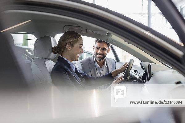 Autoverkäufer zeigt Neuwagen der Kundin auf dem Fahrersitz im Autohaus-Showroom