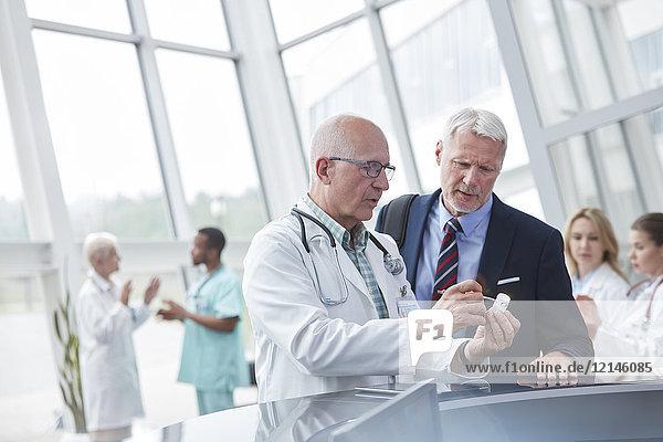 Männlicher Arzt und Pharmareferent diskutieren in der Lobby des Krankenhauses über Medikamente