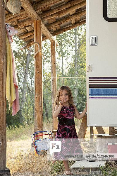 Porträt lächelndes  selbstbewusstes Mädchen im Kleid mit Geste Friedenszeichen vor dem ländlichen Wohnmobil