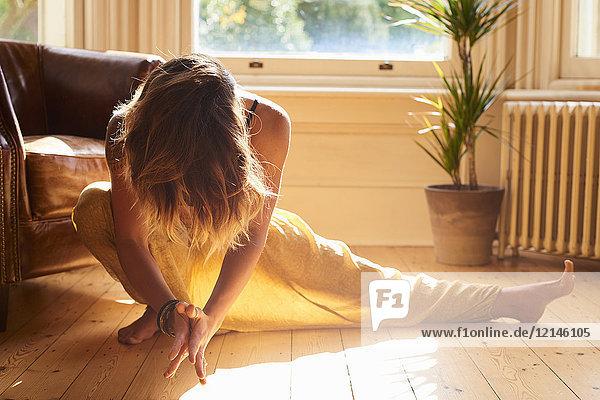 Anmutige Frau übt Yoga-Seitensprung im sonnigen Fenster