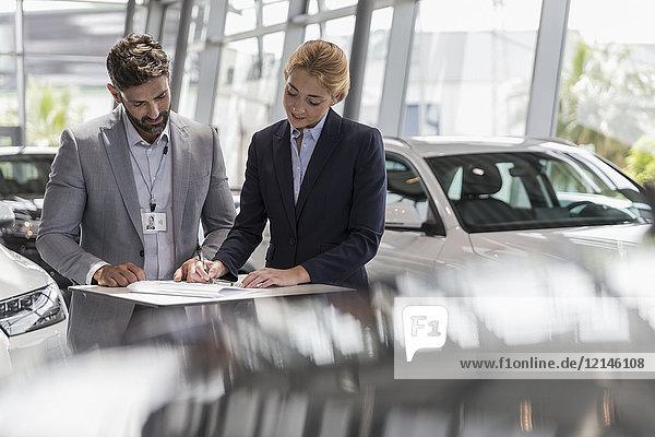 Autoverkäufer beobachtet weibliche Kunden bei der Unterzeichnung von Finanzierungsverträgen im Autohaus.