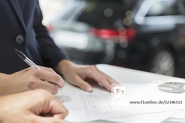 Nahaufnahme des Kunden bei der Vertragsunterzeichnung im Autohaus