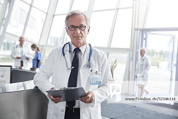 Portrait selbstbewusster Oberarzt mit Zwischenablage in der Lobby des Krankenhauses