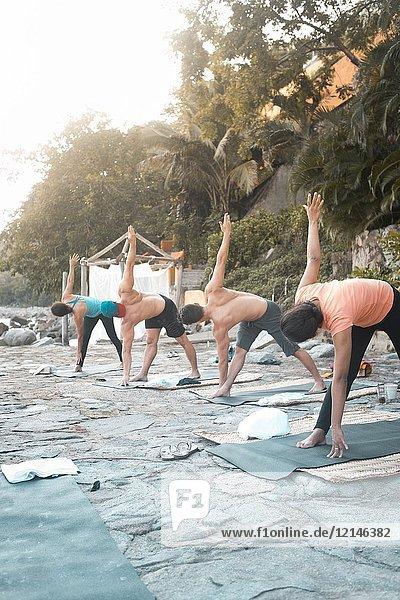 Group of multiple people exercising outdoors. Yoga retreat Puerto Vallarta - Mismaloya  Mexico.