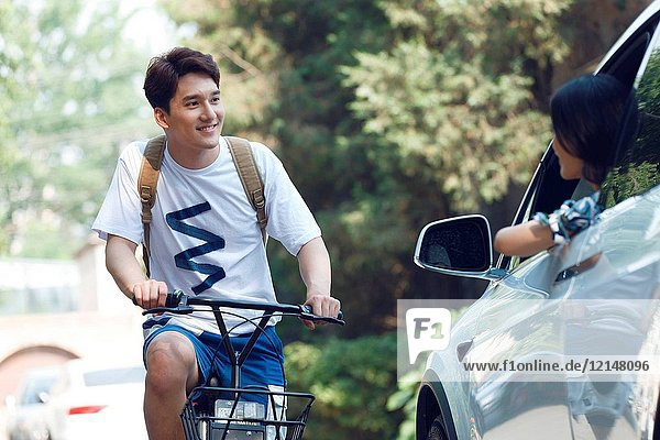 Young men ride bicycles