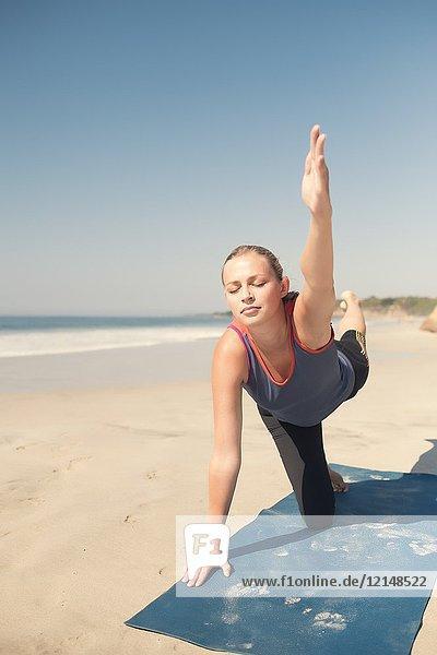 Caucasian woman exercising yoga at a beach  eyes closed.