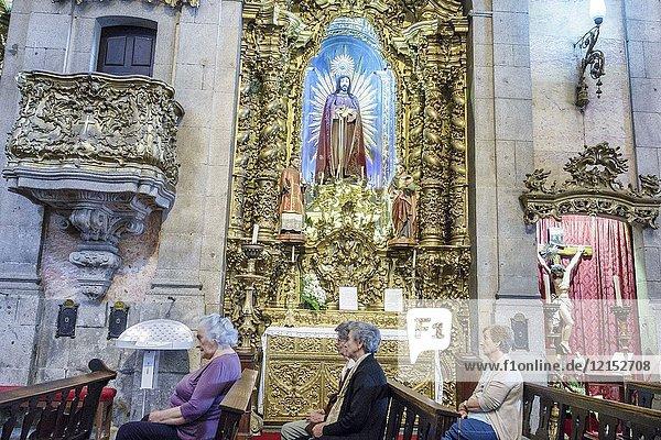 Portugal  Porto  historical center  Igreja do Carmo  church  Catholic  interior  gild  altar  Baroque  Christ  statue  Hispanic  woman  senior  pews  sitting  Portuguese Europe EU European Hispanic