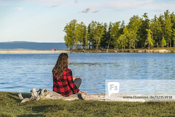 Woman with long hair and checked shirt sitting on a log on the shores of Hovsgol Lake. Hovsgol province  Mongolia.