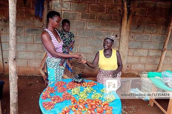 Woman buying red chili and tomatoes.