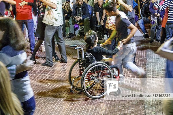 Argentina  Buenos Aires  San Telmo  Plaza Dorrego  night nightlife  tango dancers  dancing  man  woman  couple  audience  watching  performing  disabled  wheelchair  Hispanic  Argentinian Argentinean Argentine South America American