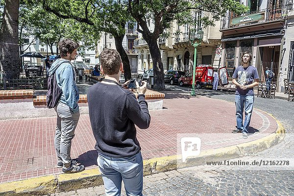 Argentina  Buenos Aires  historic center  San Telmo Plaza Dorrego  man  young adult  recording video blog  Hispanic  Argentinian Argentinean Argentine