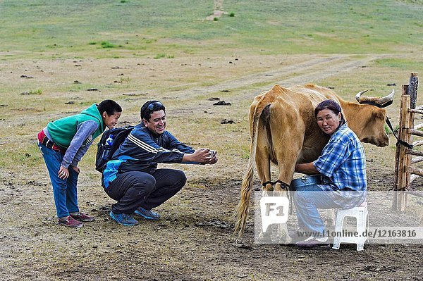 Boy watching a tourist who takes a photo with his smartphone of a female farmer who is milking a cow  Gorkhi-Terelj National Park  Mongolia.