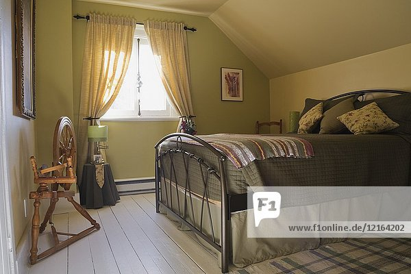 Antique wooden spinning wheel and double size bed in a bedroom on the upper floor inside an old 1877 cottage style residential home  Quebec  Canada. This image is property released. CUPR0265.