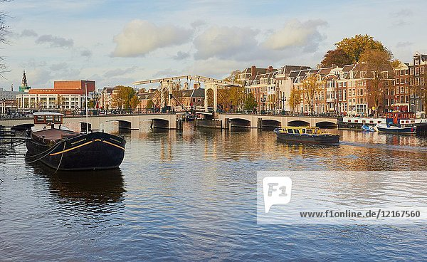 View along the Amstel River towards the Magere Brug (skinny bridge) a pedestrian and bicycle bascule bridge,  Amsterdam,  Netherlands. The current bridge was built in 1934.