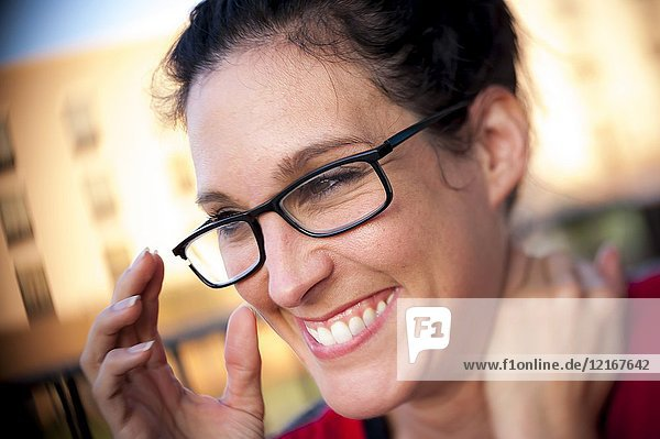 A casual portrait of a pretty 39 year old brunette woman with glasses.