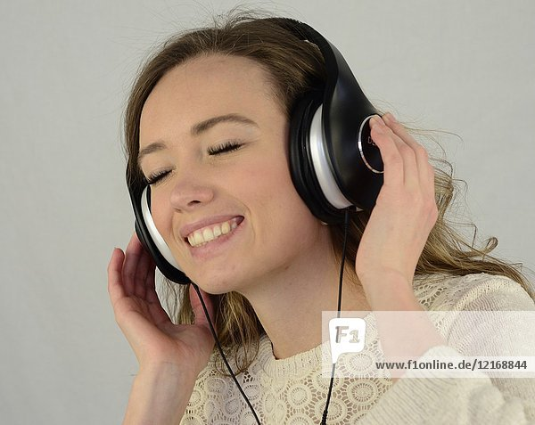 Young happy woman listening to music in headphones.