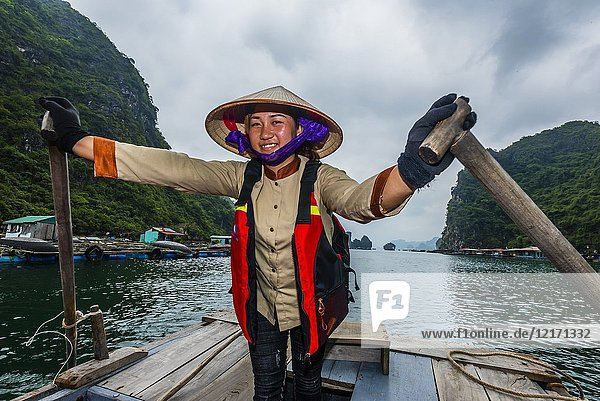 Local woman rowing a rowboat in Halong Bay  North Vietnam. The bay features 3 000 limestone and dolomite karsts and islets in various shapes and sizes sprinkled over 1 500 square kilometers. It offers a wonderland of karst topography. It is a UNESCO World Heritage Site.