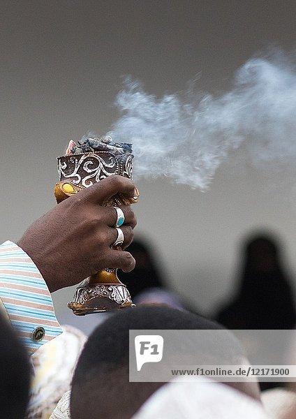 Sunni muslim man spreading insence with a censer during the Maulidi festivities in the street  Lamu County  Lamu Town  Kenya.
