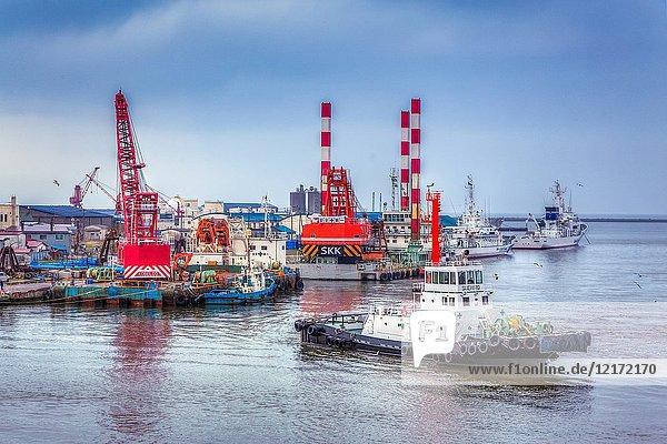 Tug boats and construction cranes in the port of Kushiro  Japan  Asia.