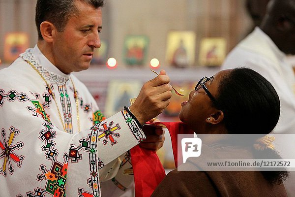 Melkite (Greek-catholic) priest giving holy communion in Sainte Foy church