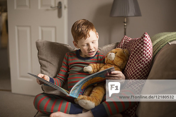 Boy reading a book on couch at home